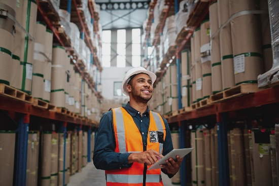 Smiling man holding tablet in warehouse