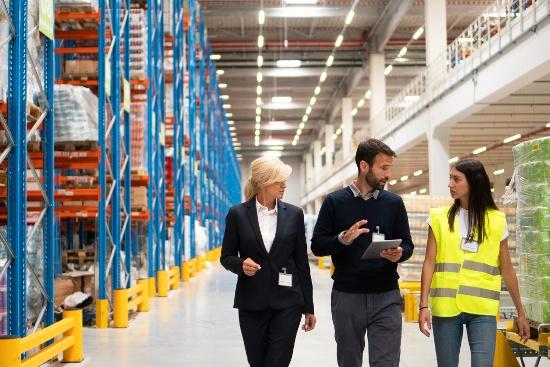 Three people walking in warehouse