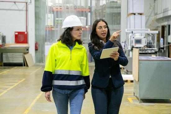 Two Women Walking in Factory