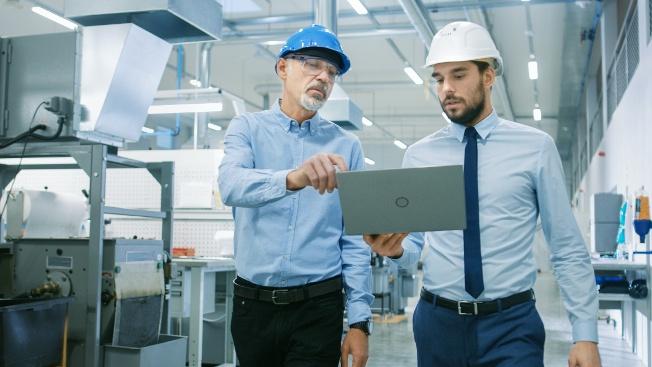 Two men wearing hard hats looking at computer
