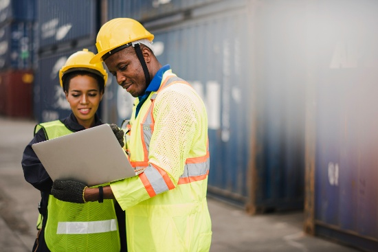 Two people in safety gear looking at tablet