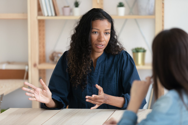 Woman talking to another woman at table